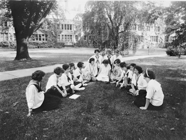 Sixteen young women wearing uniforms sit on the lawn of the college grounds.