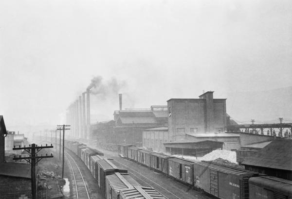 The Donora Zinc Works of the American Steel and Wire Company is dimly seen through fume-laden smoke and fog.