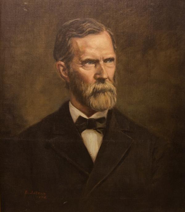 Oil on canvas portrait, head and shoulders, facing front, of a bearded, mustached, man wearing a suit coat, white shirt, and a bow tie.