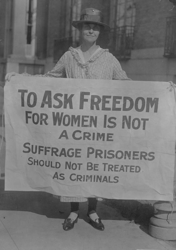 "Photograph of Mary Winsor, standing outside, holding a banner that reads: ""To Ask Freedom for Women is Not a Crime. Suffrage Prisoners Should Not be Treated as Criminals."""