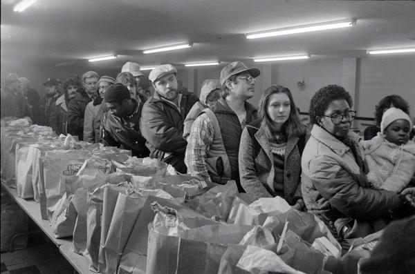 People line up to get bags of food at a food bank for unemployed steelworkers in Braddock, Pennsylvania, January 25, 1983.