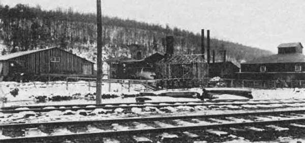 A view of several two-story buildings with several smokestacks. Visible in the foreground are railroad tracks.