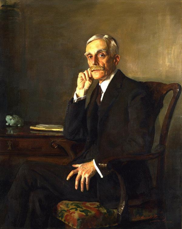 A gray haired man, with thick mustache and eyebrows, wearing a three piece dark suit, white shirt, and tie sits in a chair at a desk. His right hand leans against his chin and his left lies on his leg.