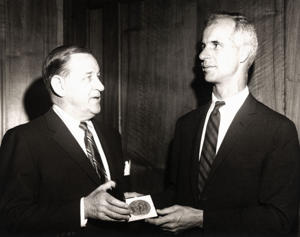 O'Hara is receiving an award from John Hershey, as both men stand face to face.