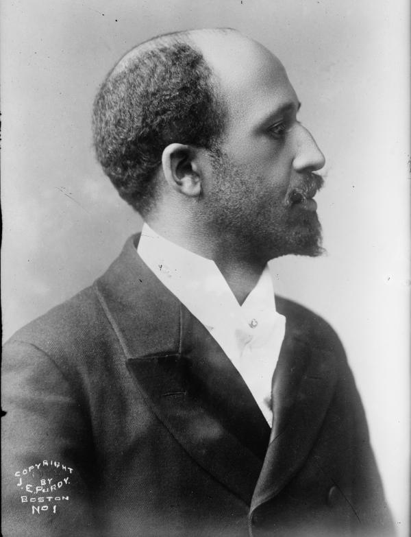 Black and white photograph, head and shoulders of a balding man, with a mustache and short beard.