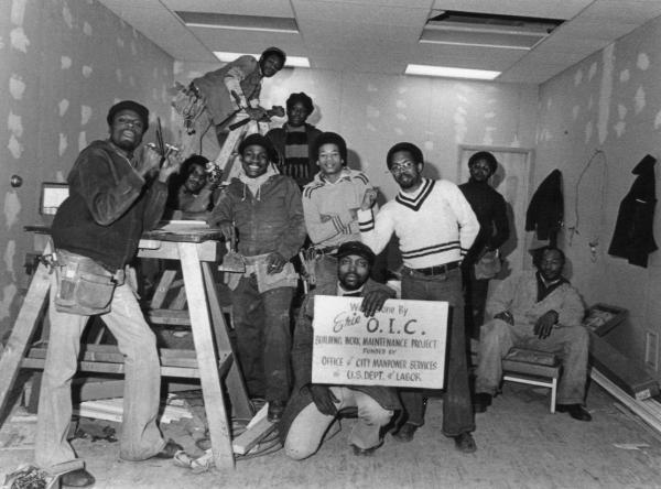 Male workers pose for this photo and one of them holds an O.I.C. sign.