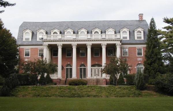 Exterior, front facade, neo-classical style.  Red brick, trimmed with limestone, with large Corinthian columns supporting the front porch.