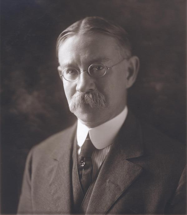 Black and white, head and shoulders image of man with a mustache, wearing spectacles, a suit with a vest and a tie.