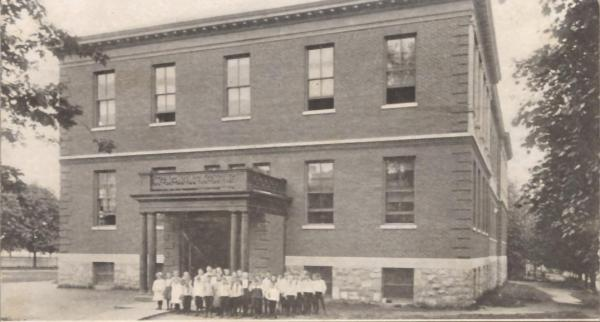 Exterior with students posing next to the school.