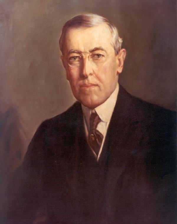Oil on canvas of Wilson, wearing a dark suit, shite shirt, and a drak tie. Head and shoulders.