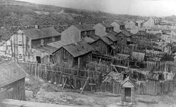 A row of several very rustic two-story houses, each with small yards separated by plank fencing. Also visible are several outhouses.