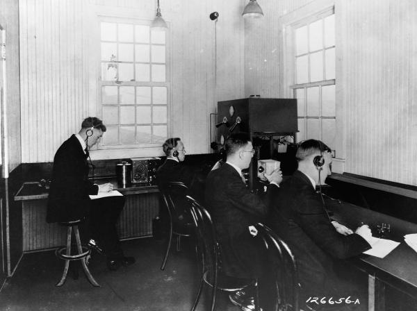 Four male radio broadcasters sit at desk in a staion room.