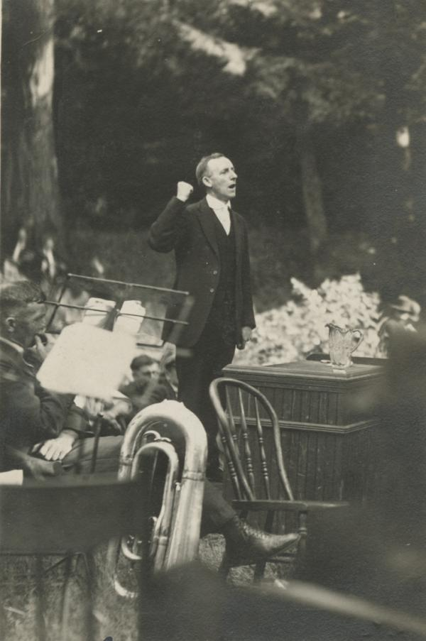 Photograph of John Brophy, arm raised in the air and his fist clenched, speaking at an outdoor gathering.