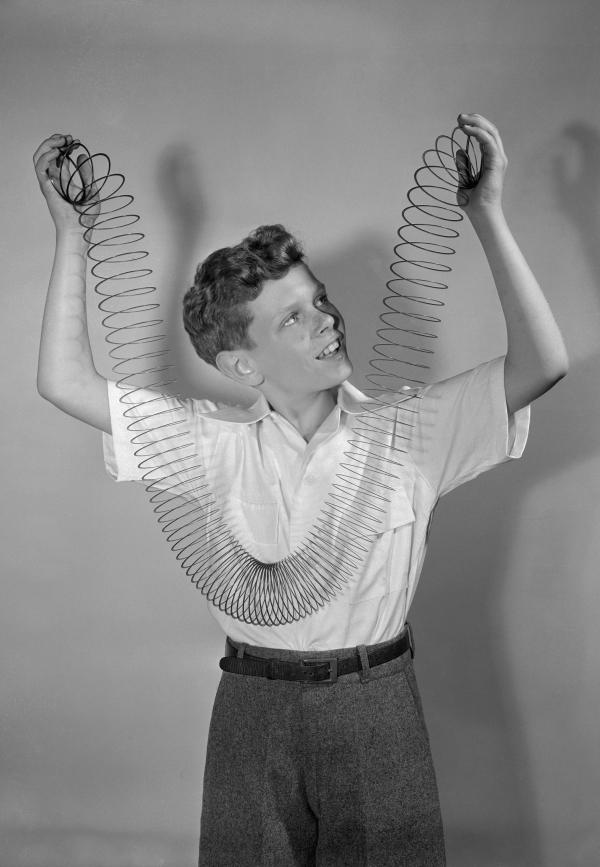 A  young boy plays with a slinky.