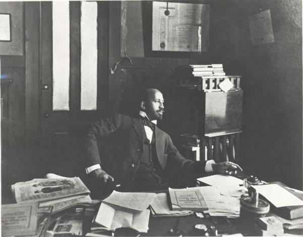 W. E. B. Dubois seated at a desk, in the office of The Crisis