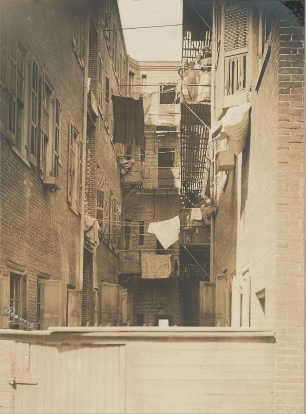 Tenement housing on both sides of a narrow alley. Laundry hangs between the two buildings. In the top right, a mother and children pose on a balcony