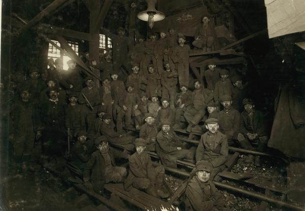 Group of breaker boys pose for a group picture at their work benches.
