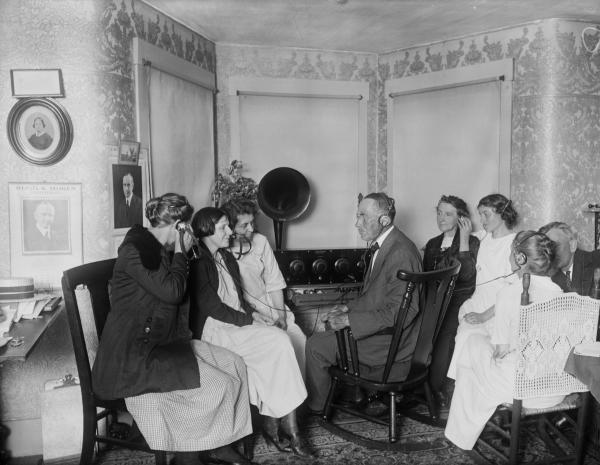 A small group of people, sitting in chairs and wearing headphones, are listening to a radio broadcast.
