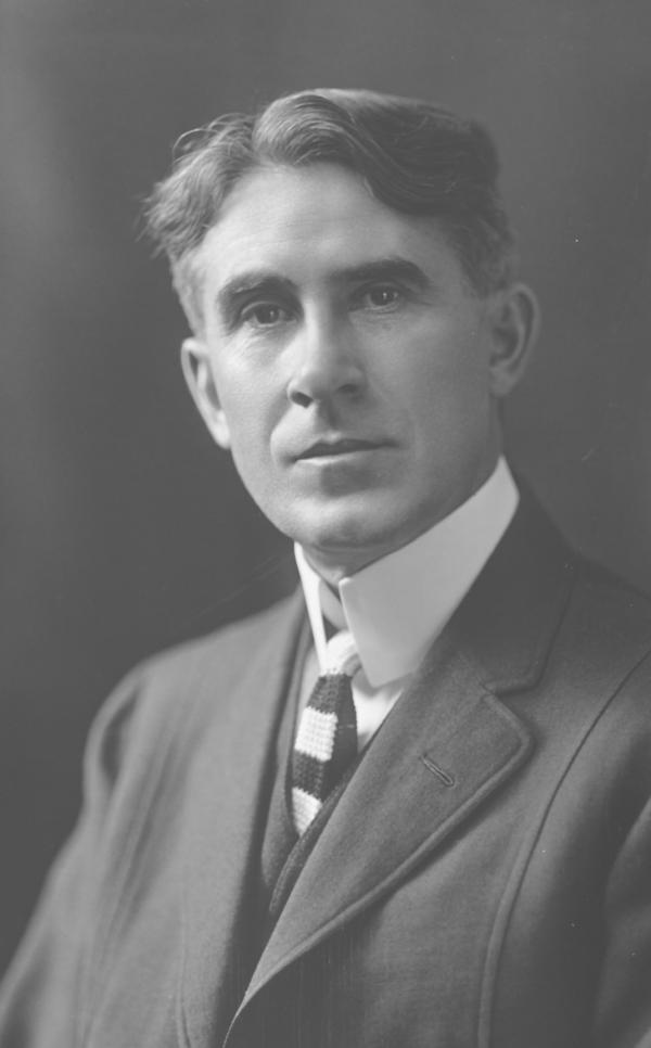 Head and shoulders, wearing a suit and tie, black and white photo.