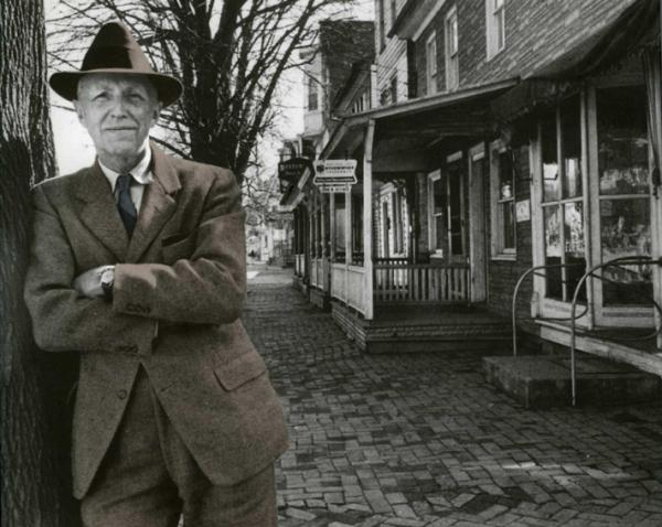 A man wearing a hat, suit, and tie leans against a tree with his arms crossed. A bricked sidewalk and row houses are to the right.