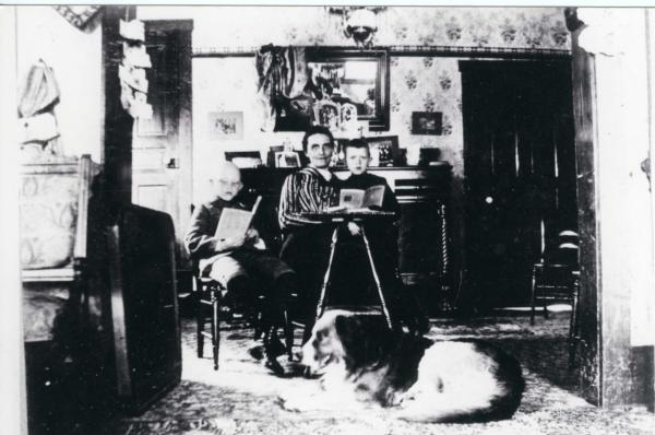 Lottie Richter and her younger sons Joe and Fred, with the family dog Dixie, sitting inside the house.