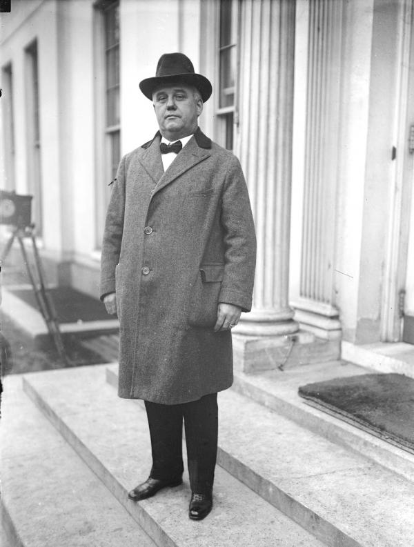 A man standing outdoors in front of a government building
