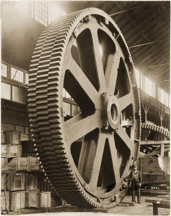 Worker standing beside a staggered tooth gear, Mesta Machine Company, West Homestead, PA, 1913.