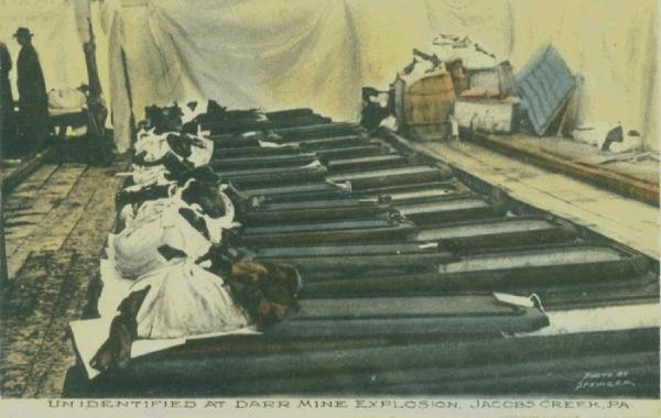 The bodies of the miners killed, their clothes piled on the caskets, lay side by side waiting to be identified