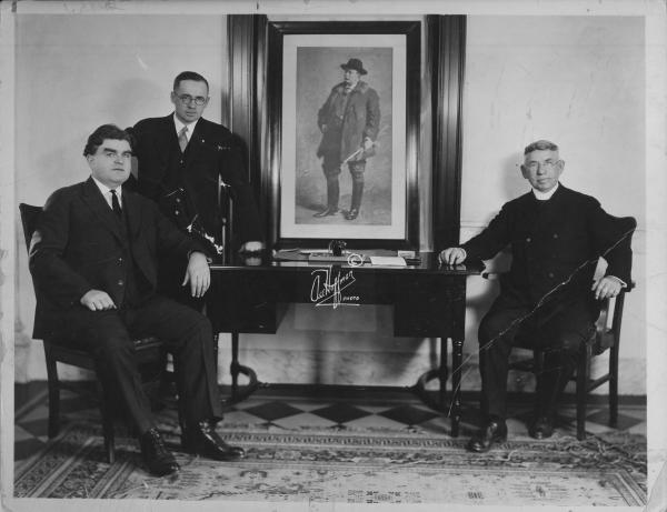 Three men. One standing and two seated.