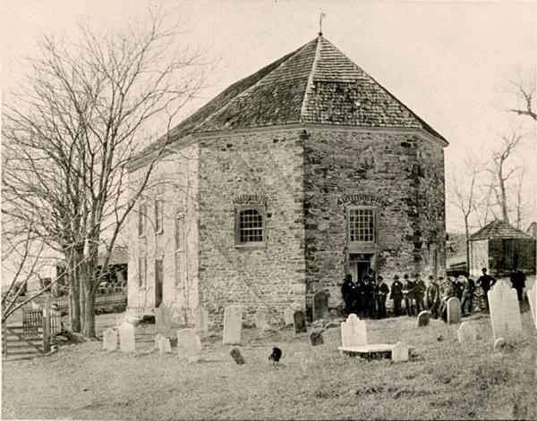 Exterior image of the church, grounds, graves, and members.
