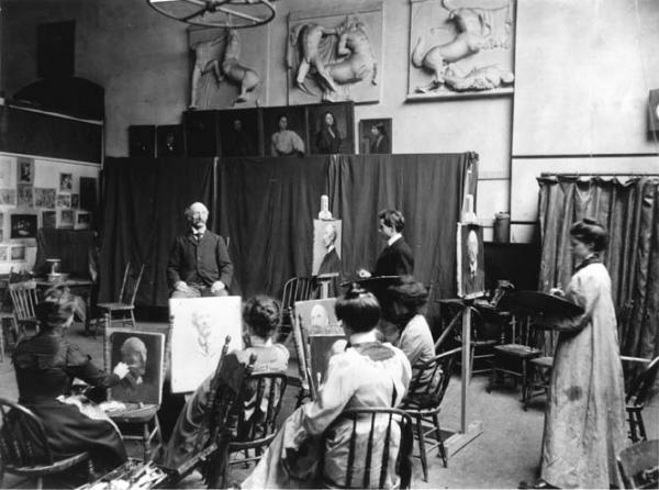 Photograph of an early class with students.   An elderly gentleman poses for students. Five students sit in chairs in front of their easels, while two stand. Art is stored throughout the room.