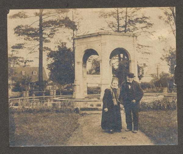 Black and white image of a man and woman standing side by side in front of a pavilion.