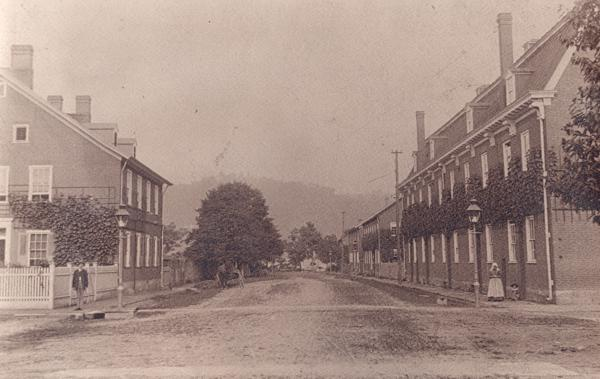 Street scene with buildings on either side of a dirt road.