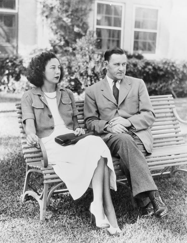 American writer John O'Hara sitting with his wife Belle on a bench.