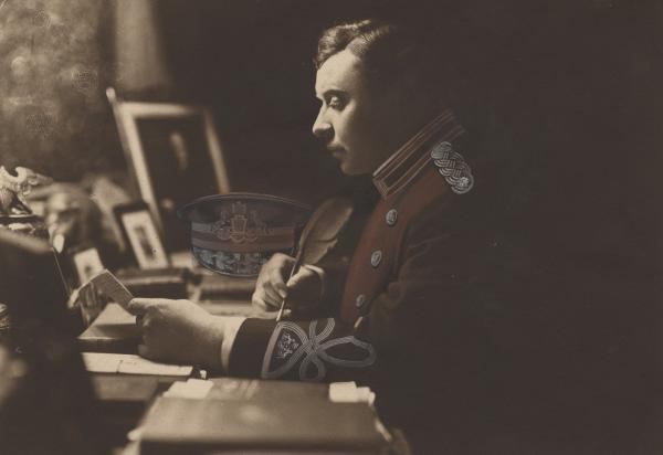 Henry Shoemaker is seated at his desk, writing with a feather-pen. It is a side view shot, and he is wearing a military uniform.