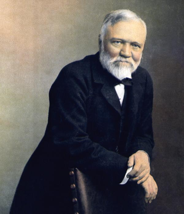 Formal portrait of Andrew Carnegie standing and leaning on the back of a leather chair.