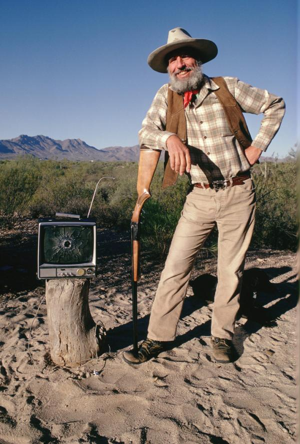 Edward Abbey with his shotgun and freshly bagged television complete with a bullet hole through the screen.