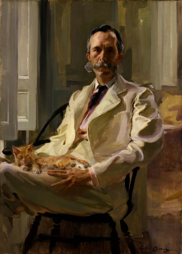 A man wearing a white suit, sits in a chair and holds a cat in his lap.