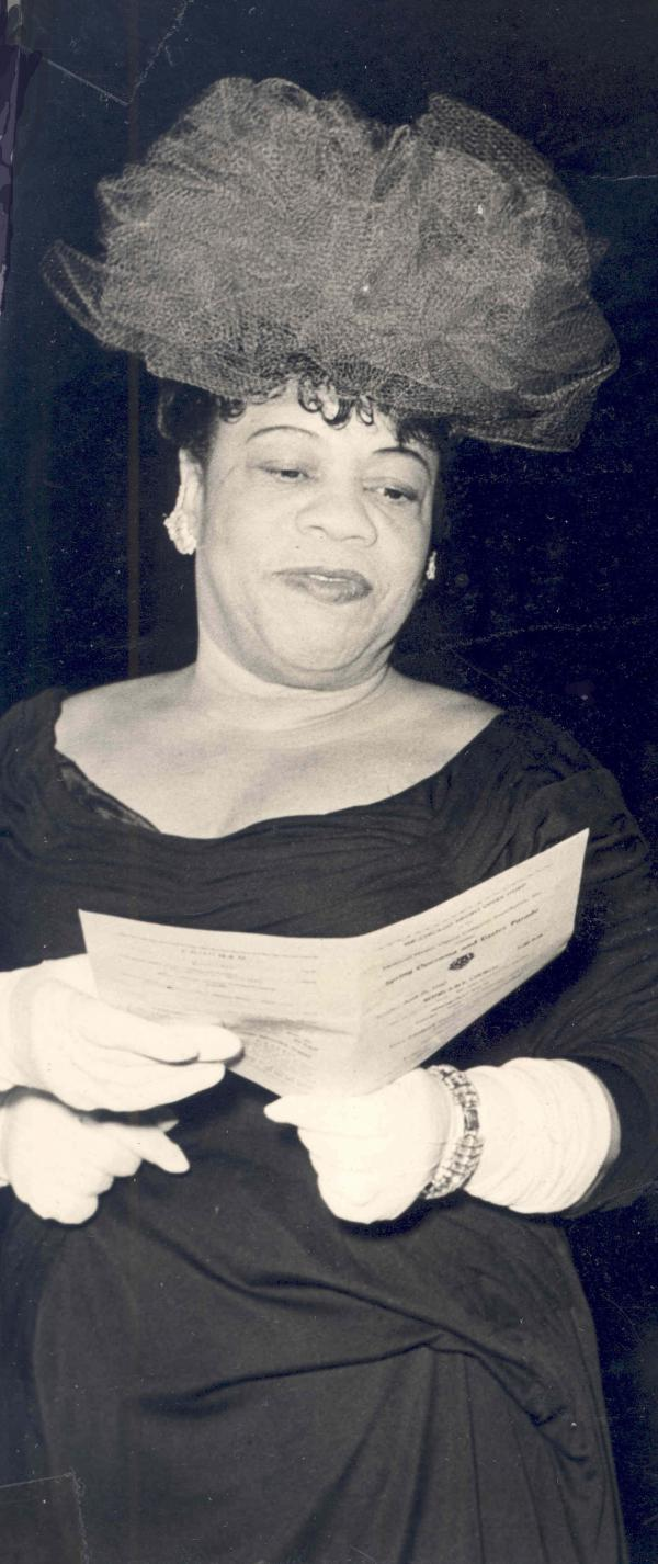 Black and white photograph of an African-American woman holding a program. She is wearing a large veiled hat and a dress.