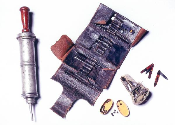 Medical Equipment with syringe, small knives, and needles in a leather case.