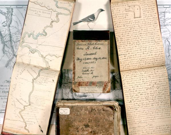 "Collage of Lewis  and Clark journals: in the background is the map of their trip; open journal on the left with river is ""draught of the falls and portage of the Missouri River;"""