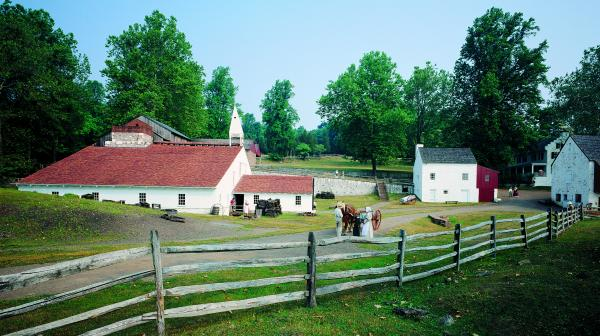 Village scene of Hopewell Village. A gray wooden fence stretches along the entire foreground of the photograph. There is a white barn, with a red roof and a steeple, to the left and a white house with a gray roof and red addition in the right. In the background one can see a stair way that leads upward along the side of a stone wall. Two adults and a child stand beside a horse and wagon near the fence and other humans are standing in the doorway of the barn, beside the stone wall, and along the side of the barn.