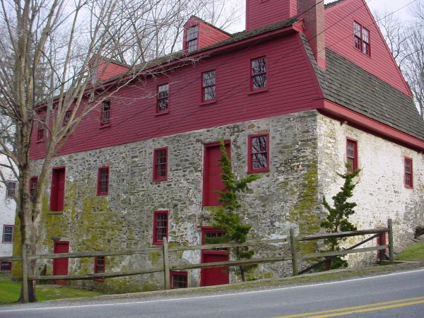 Color image of Newlin Grist mill exterior. Large stone building with red wood on the top floor and red trim around all windows and doors.
