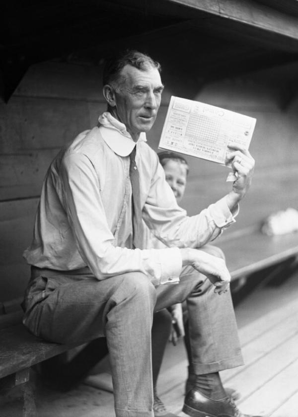 Connie Mack sits in the dugout holding a scorecard.