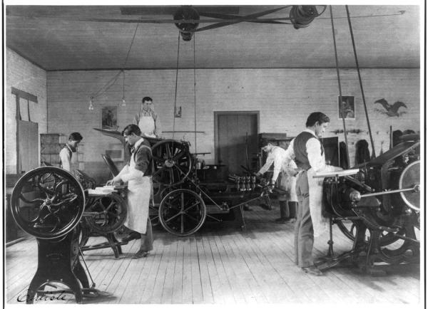 Printing Room at Carlisle School, by F. B. Johnson, 1901, depicting a group of Native American boys standing in long aprons at several antique looking printing presses.
