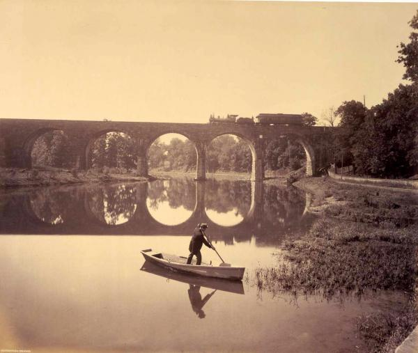 William H. Rau Photograph of Conestoga Bridge, 1891.   A lone man stands in his boat and pushes it along the water with an oar. A train passes over the Conestoga Bridge as the sun casts shadows of the bridge, the train, the man, and his boat.