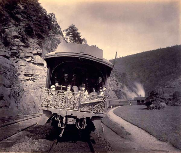 Observation End of the Penna. Limited, on the Horseshoe Curve, by William Rau. Passengers dressed in their finery, sit outside, at the rear of the train, as it travels around the Horseshoe Curve.