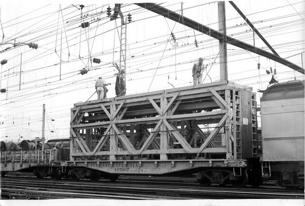Track Electrification photograph. Many wires, cables, and transformers stretch above the railroad track.
