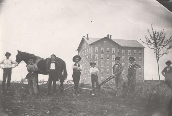 Image of a building exterior and five young men farming the land in the foreground. Horse and plow are visible.