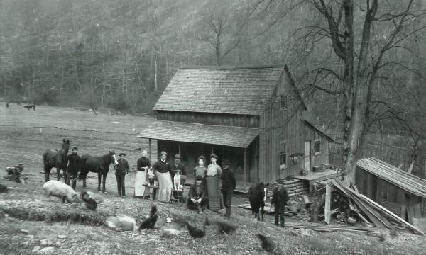 A farm family posing for a photograph. Family, pets, and and livestock pose in front of the home.